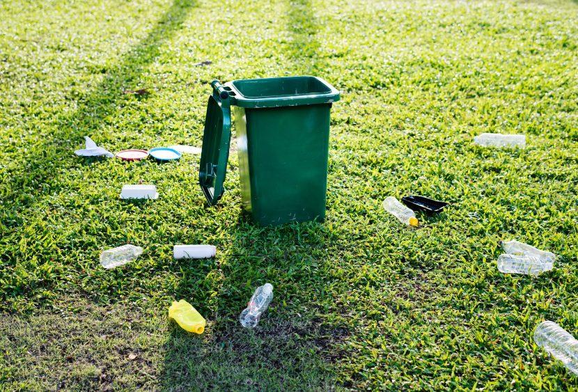 offene Mülltonne auf einer Wiese mit Plastikflaschen